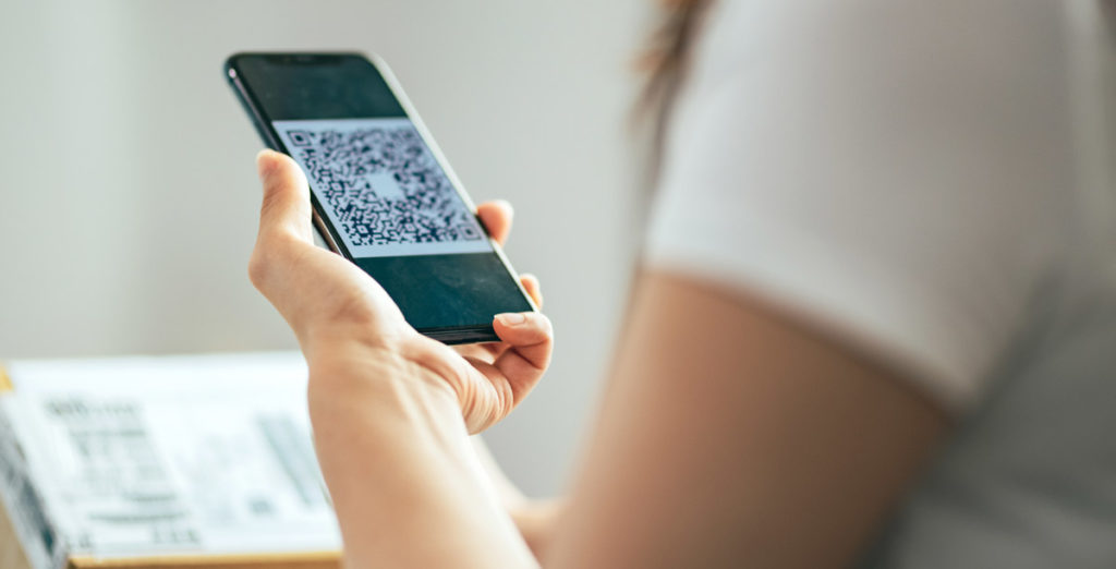 women scanning qr code from mail parcel package